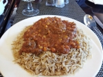 A hefty plate of palau, which is seasoned lamb under a pile of saffron rice and served with a meat sauce on top.
