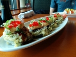 The Godzilla Roll: deep fried roll with salmon and yellowtail, topped with Sriracha mayo, tobiko, scallions, and eel sauce.