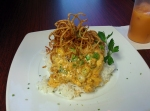 The Curry Chicken Bombay: two fried chicken breasts smothered with a yellow curry sauce, topped with scallions, crispy noodle straws, and served over a bed of rice.