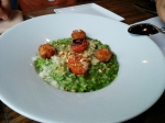 Risotto Caprese with an arugula base, topped with cherry tomatoes, crispy mozzarella balls, and crushed hazelnuts